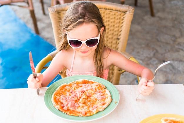 Kleines mädchen, das pizza auf abendessenzeit isst