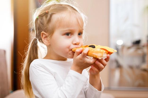 Kleines mädchen, das pizza isst
