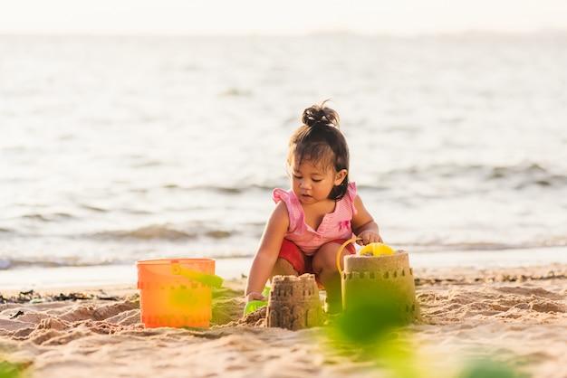 Kleines mädchen, das sand mit spielzeugsandwerkzeugen spielt