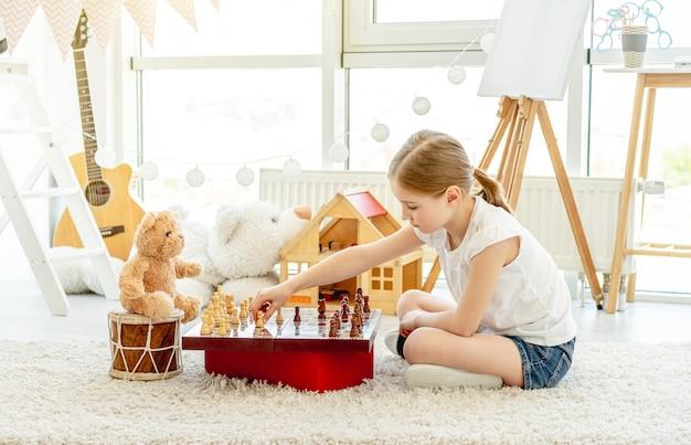 Kleines mädchen, das schach mit teddy spielt