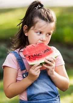 Kleines mädchen, das scheibe der wassermelone genießt