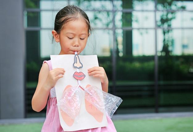 Kleines mädchen, das schlag mit spielt, simulieren das atmen der lungen. gesundheitswesen-konzept.