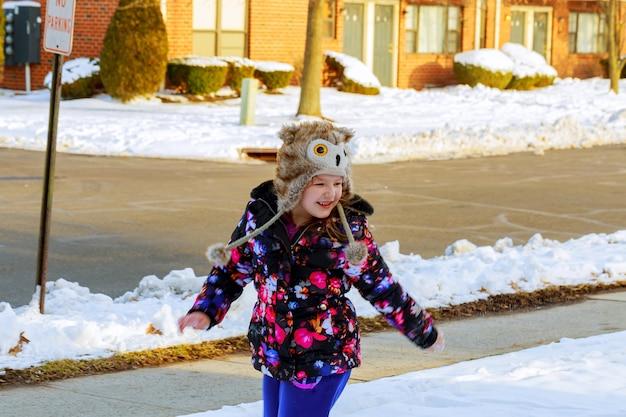 Kleines mädchen, das schnee auf hauptantriebsweise schaufelt. schöner verschneiter garten oder vorgarten.