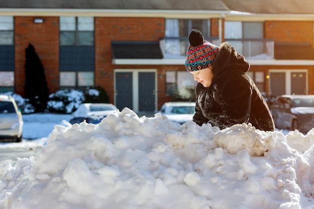 Kleines mädchen, das schnee auf hauptfahrstraße schaufelt. schöner verschneiter garten oder vorgarten.