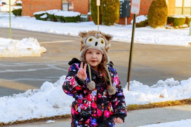 Kleines mädchen, das schnee auf hauptfahrweise schaufelt. schöner schneebedeckter garten oder vorgarten.