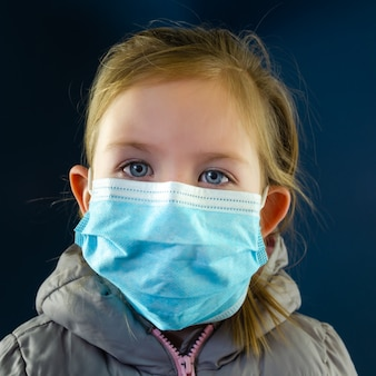 Kleines mädchen, das schutzmaske im konzeptuellen bild des ausbruchs des koronavirus trägt.