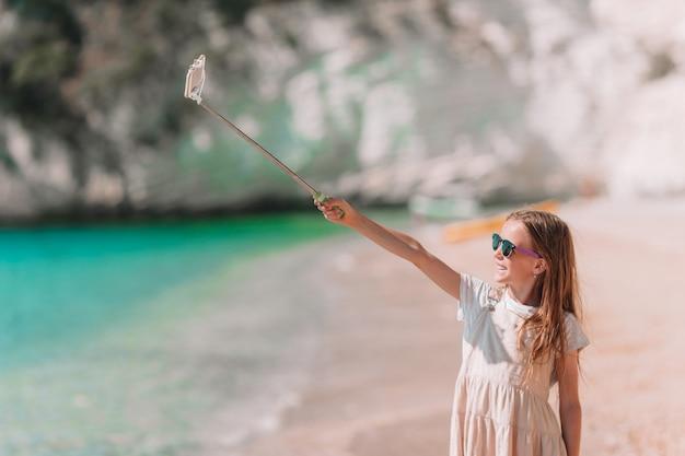 Kleines mädchen, das selfie durch ihren smartphone auf dem strand nimmt.