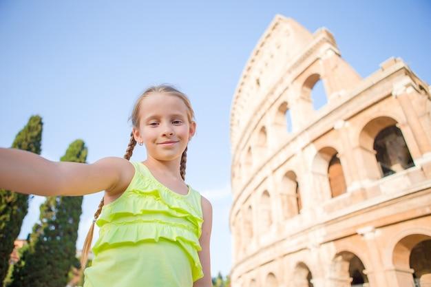 Kleines mädchen, das selfie hintergrund kolosseum, rom, italien macht. kinderporträt an berühmten orten in europa
