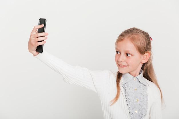 Kleines mädchen, das selfie mit smartphone nimmt