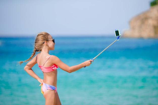 Kleines mädchen, das selfie porträt mit ihrem smartphone nimmt