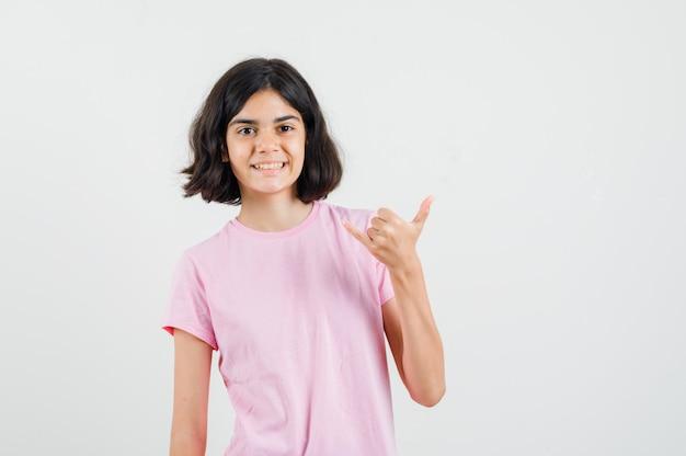 Kleines mädchen, das shaka zeichen im rosa t-shirt macht und froh schaut, vorderansicht.