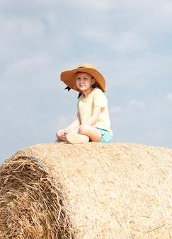 Kleines mädchen, das sich an einem sommertag auf einem weizenfeld amüsiert. kind, das während der erntezeit am heuballenfeld spielt.