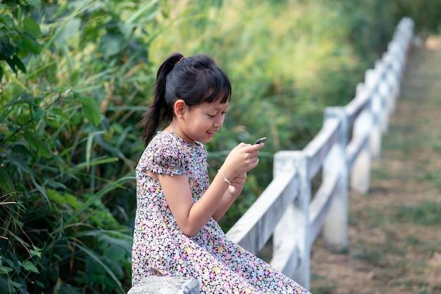 Kleines mädchen, das smartphone mit lächeln benutzt