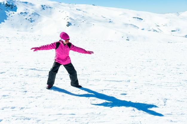 Kleines mädchen, das snowboardtrainer auf schnee spielt
