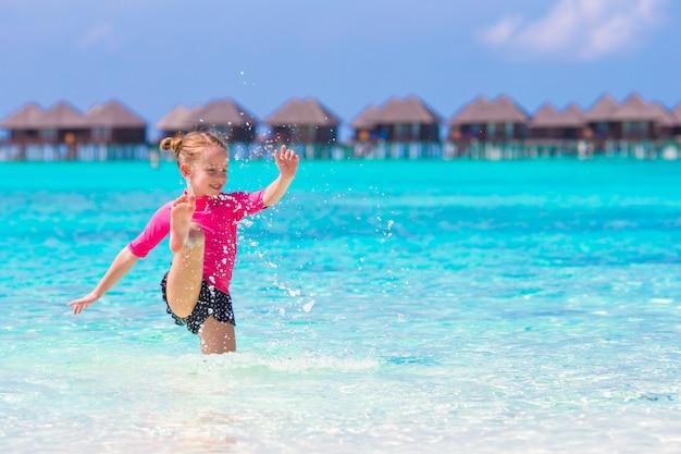 Kleines mädchen, das spaß auf tropischem strand mit türkisozeanwasser hat
