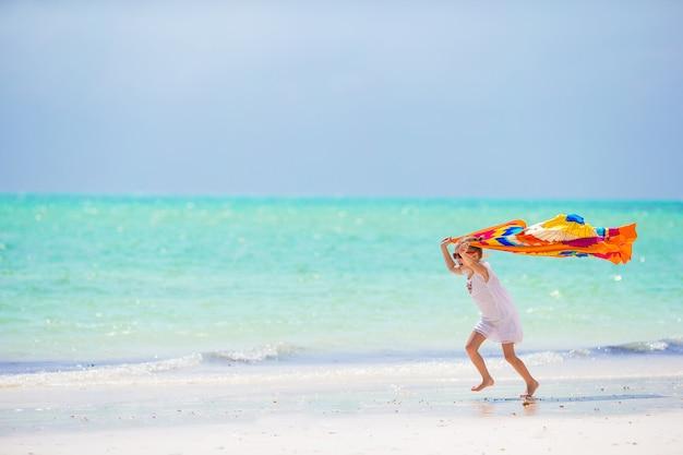 Kleines mädchen, das spaß hat, mit pareo auf tropischem strand zu laufen