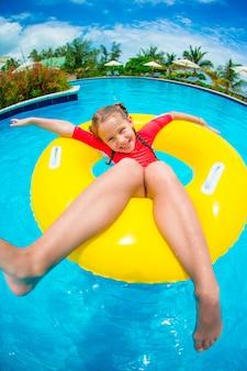 Kleines mädchen, das spaß im aufblasbaren gummikreis am swimmingpool hat. familiensommerferien, kind entspannen sich am pool.