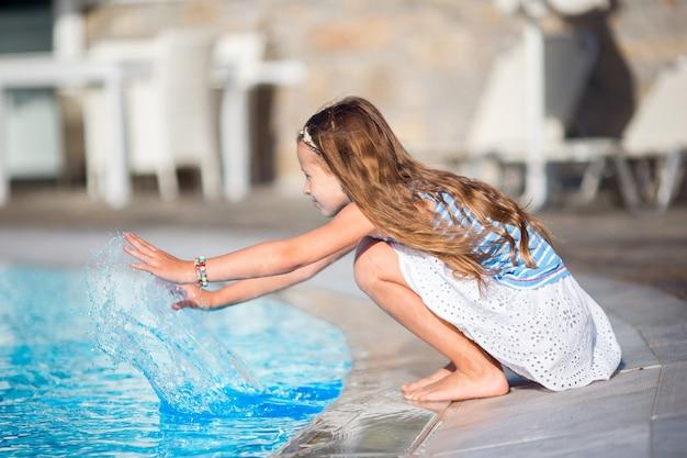 Kleines mädchen, das spaß mit einem spritzen nahe swimmingpool hat