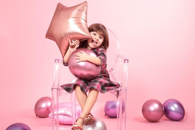 Kleines mädchen, das spaß mit luftballons und konfetti hat. das konzept von feier und spaß.