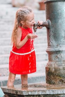 Kleines mädchen, das spaß mit trinkwasser am straßenbrunnen in rom, italien hat