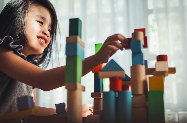 Kleines mädchen, das spielbaukonstruktorturm aus bunten holzklötzen spielt. lern- und entwicklungskonzept.