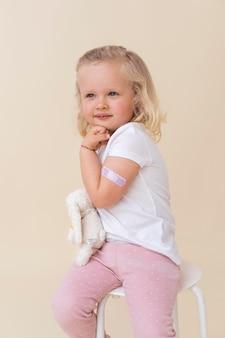 Kleines mädchen, das spielzeug hält, nachdem es einen impfstoff erhalten hat