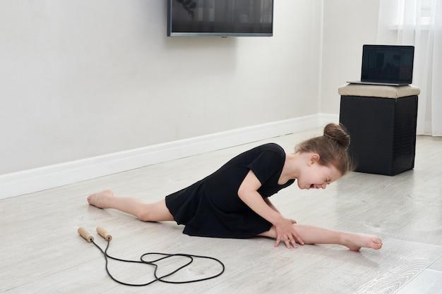 Kleines mädchen, das split- und gymnastikübung zu hause macht und viel schmerz fühlt