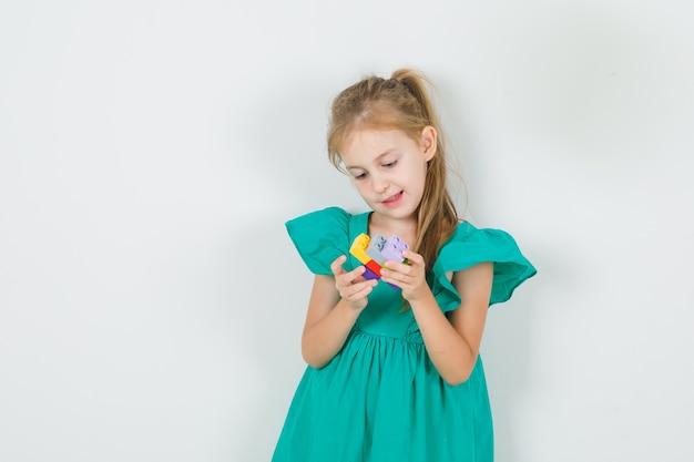 Kleines mädchen, das stapel von spielzeugblöcken in der vorderansicht des grünen kleides hält.