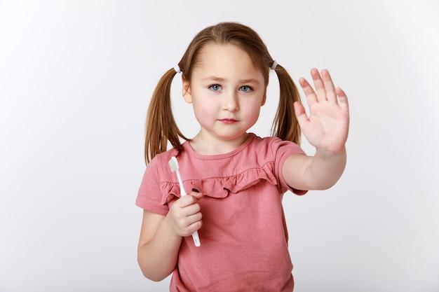 Kleines mädchen, das stopp zeigt, vergessen sie nicht, ihre zähne zu putzen