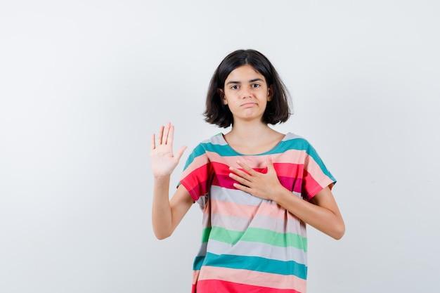 Kleines mädchen, das stoppschild zeigt, während es die hand auf der brust in t-shirt, jeans hält und unzufrieden aussieht. vorderansicht.