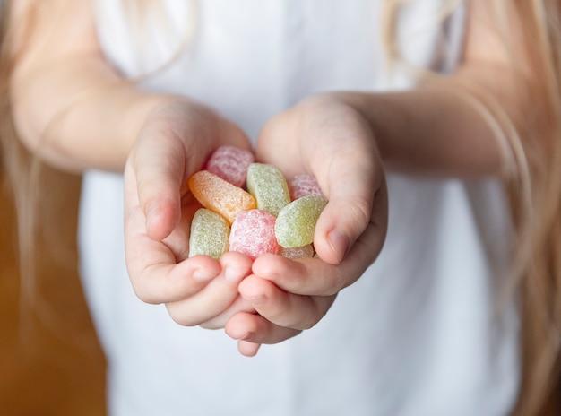 Kleines mädchen, das süße bonbons in ihren händen hält