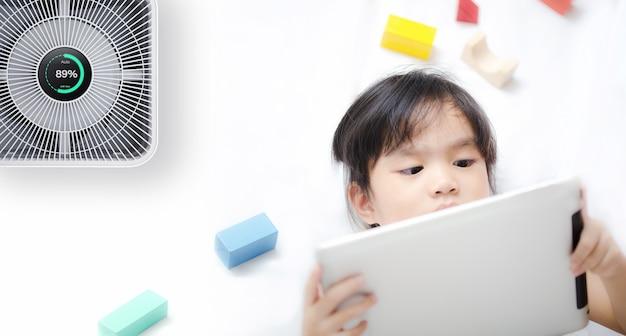 Kleines mädchen, das tablette im raum mit modernem luftreiniger verwendet