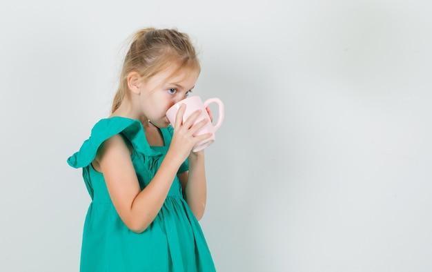 Kleines mädchen, das tasse tee im grünen kleid trinkt und durstig aussieht. .
