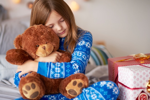 Kleines mädchen, das teddybär in weihnachten bindet