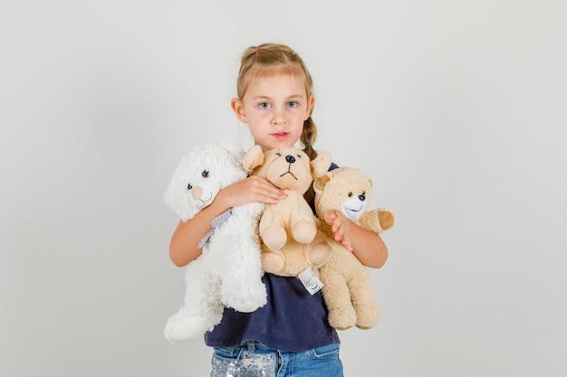 Kleines mädchen, das teddybären hält und kamera in der vorderansicht des t-shirts und des jeansrockes betrachtet.