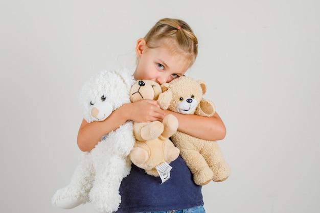 Kleines mädchen, das teddybären umarmt und in t-shirt und jeansrock, vorderansicht lächelt.