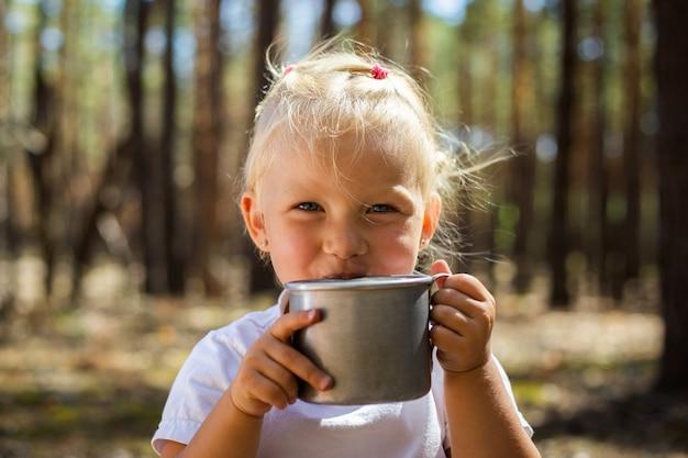 Kleines mädchen, das tee oder saft während eines haltes im wald streichelt. gehen sie mit den eltern. mit den eltern spazieren gehen.