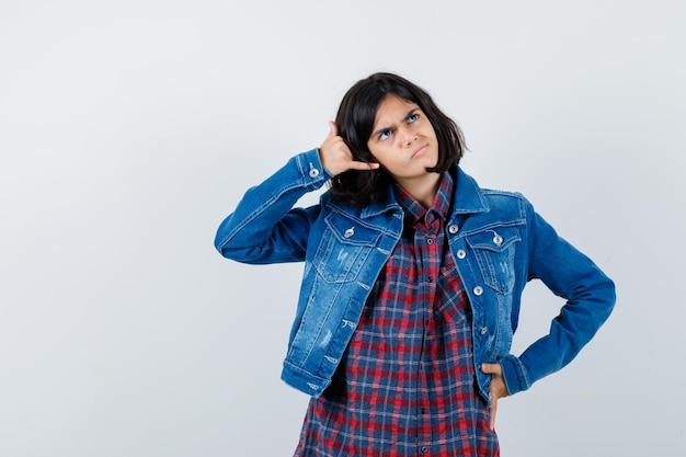 Kleines mädchen, das telefongeste in hemd, jacke zeigt und nachdenklich aussieht. vorderansicht.