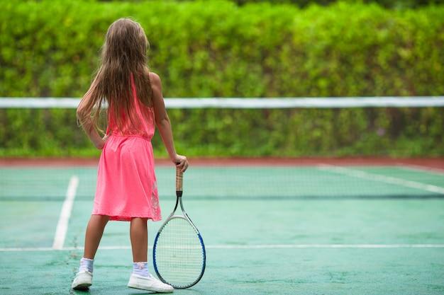 Kleines mädchen, das tennis auf dem gericht spielt