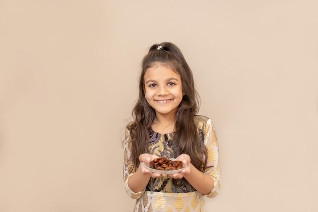 Kleines mädchen, das traditionelles pakistanisches kleid trägt und ramadan kareem feiert. hält teller mit datteln. iftar zeit.
