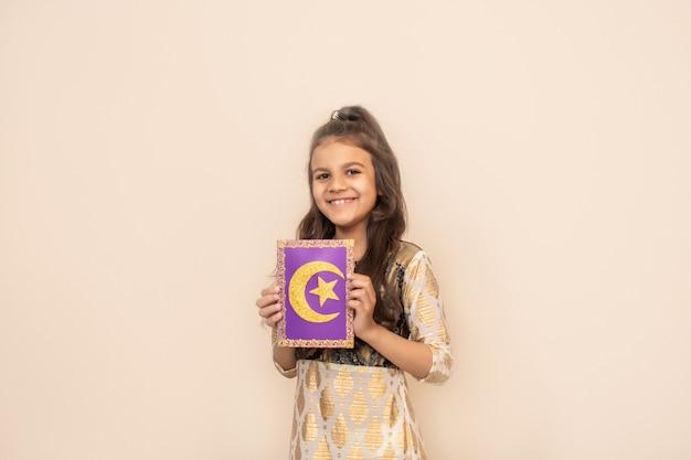 Kleines mädchen, das traditionelles pakistanisches kleid trägt und ramadan kareem feiert.