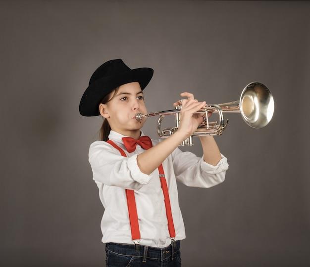 Kleines mädchen, das trompete auf grau spielt