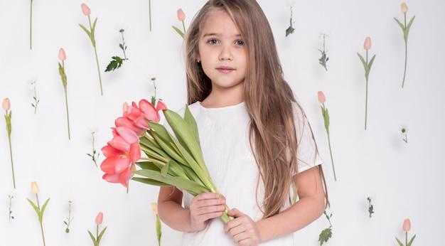 Kleines mädchen, das tulpenblumenstrauß hält