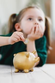 Kleines mädchen, das über ihre geldausgabe nachdenkt und eine münze in ein sparschwein steckt