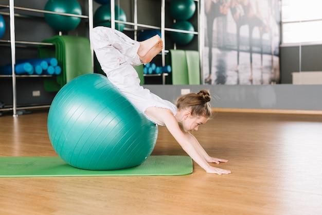 Kleines mädchen, das übungen mit dem trainieren des balls in der eignungsturnhalle tut