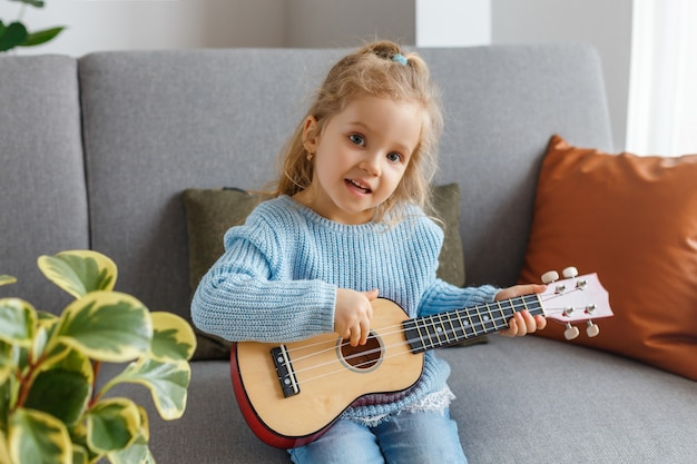 Kleines mädchen, das ukulele spielt und zu hause singt. kind lernt gitarre. frühkindliche erziehung
