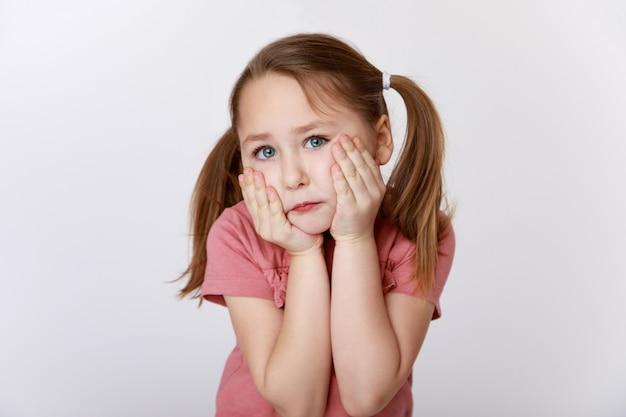 Kleines mädchen, das unter zahnschmerzen leidet, die ihre wange halten