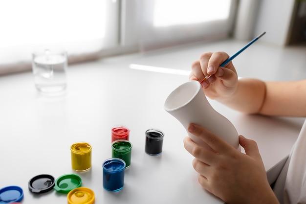 Kleines mädchen, das vase zu hause malt