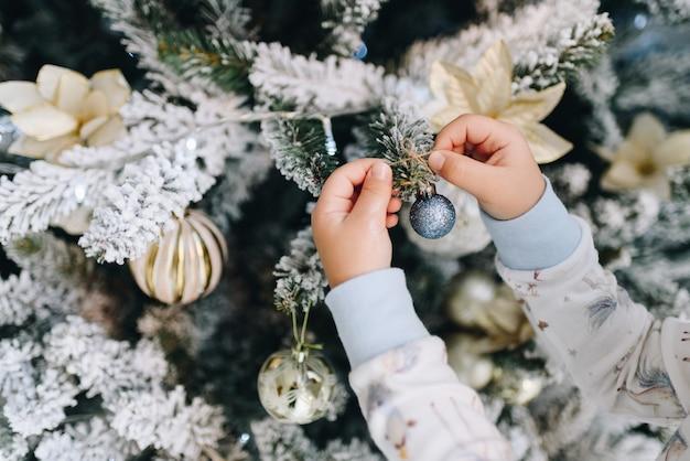 Kleines mädchen, das verzierungen auf weihnachtsbaum setzt