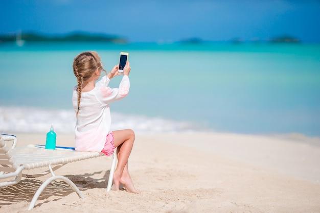 Kleines mädchen, das video oder foto mit durch ihre kamera sitzt auf dem sunbed macht